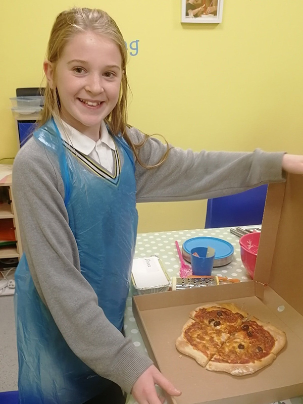 Proud girl showing off her pizza she made