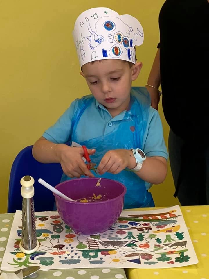 Boy with chefs hat cooking